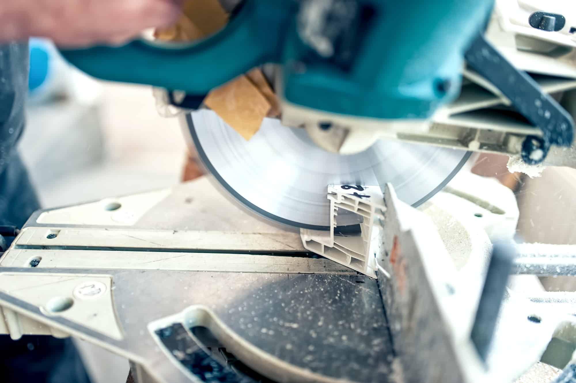 worker or handyman cutting PVC profile with circular saw, sliding saw